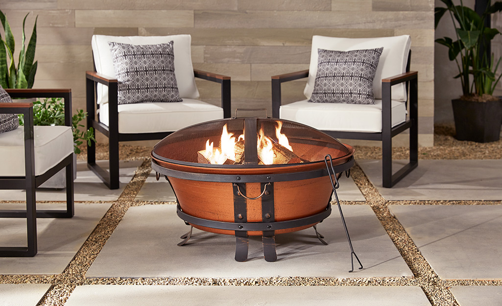 A cast iron fire pit with a copper finish on a patio with outdoor furniture.