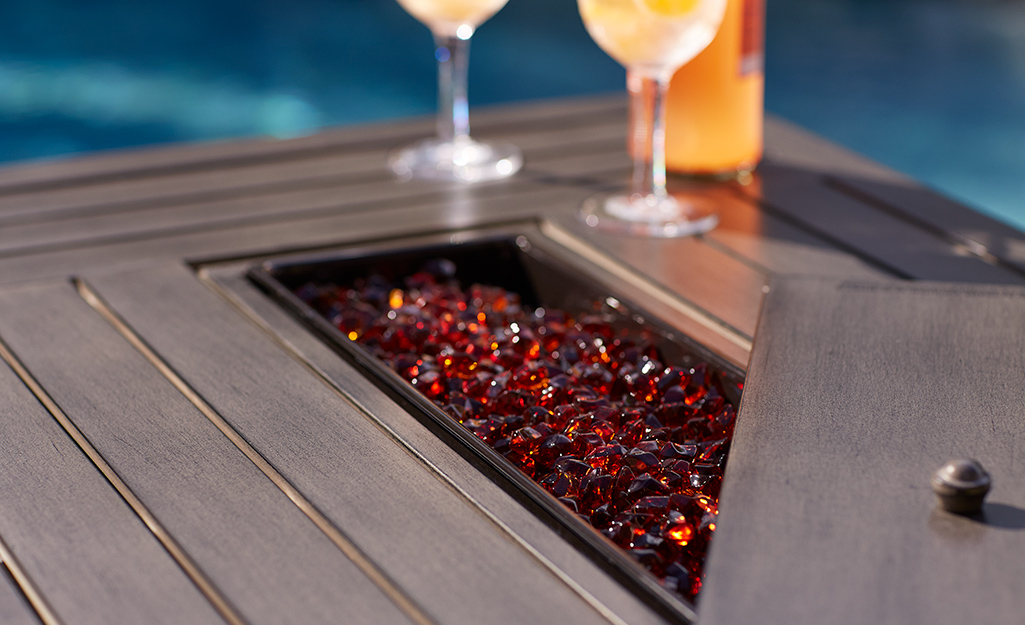 Red fire glass in the flame area of a fire pit table.