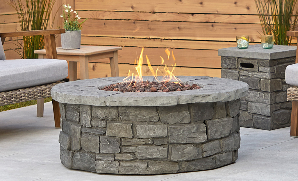 Stone fire pit on a patio with wooden walls.