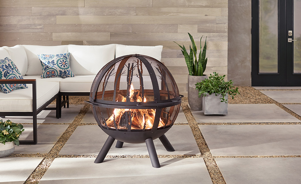 Round, metal wood-burning fire pit on a patio with white-cushioned sectional.