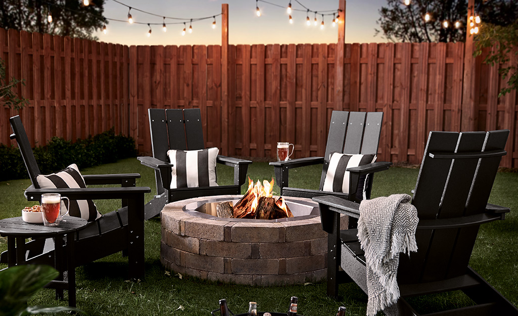 A stone block fire pit with Adirondack chairs in a fenced back yard.