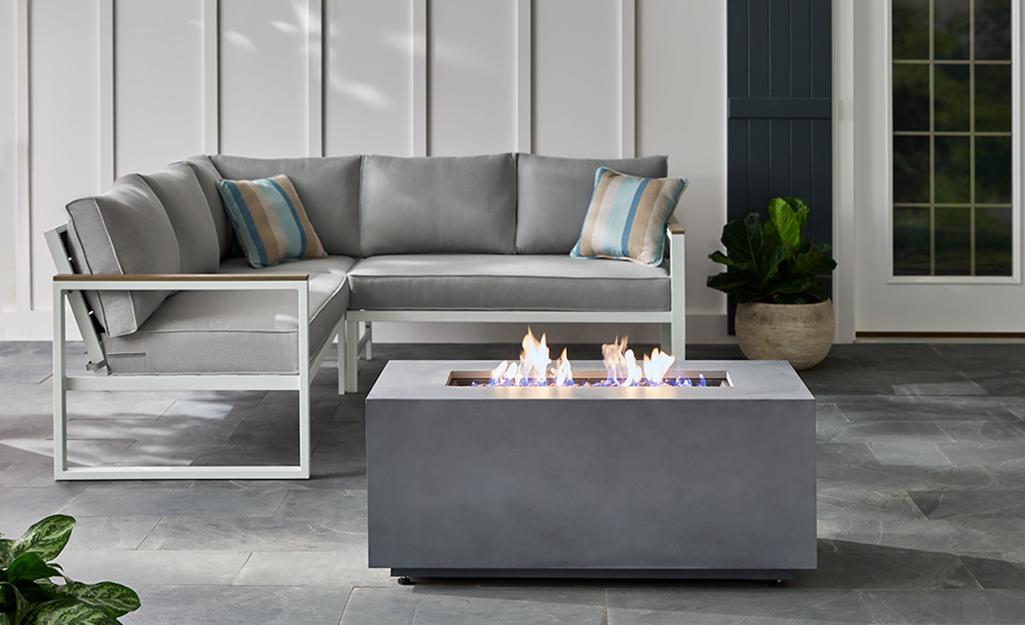 Modern rectangular stone fire pit on a patio.