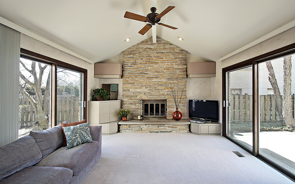 A wood-burning, stone fireplace in a contemporary living room.