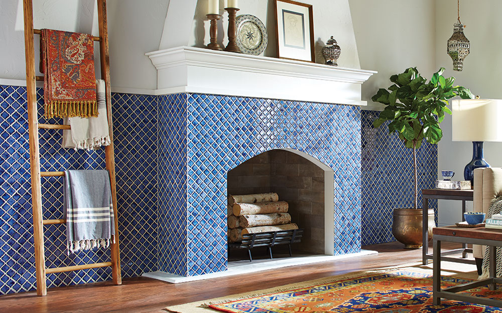 A blue tiled living room fireplace topped with a white mantel