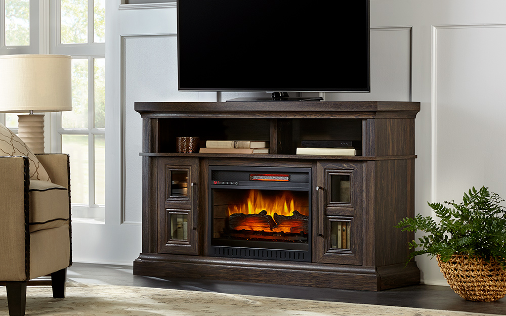 Electric fireplace in a media center with a TV on top.