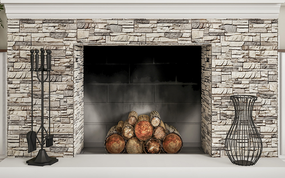 Black metal fireplace accessories beside a wood-burning fireplace.