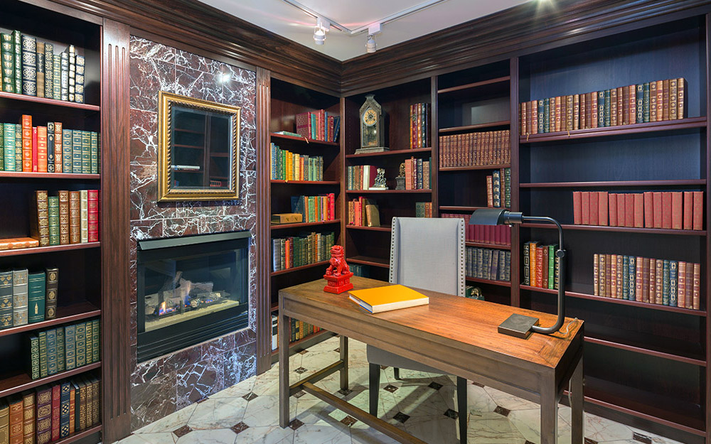 A home library filled with books and a built-in fireplace with a brown marble surround.