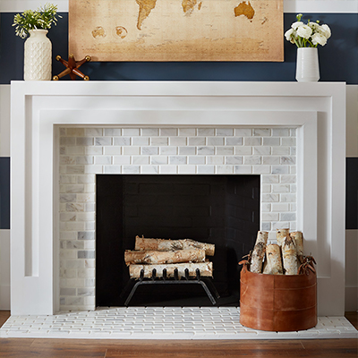 A white brick fireplace with firewood stacked on a grate and a basket of more firewood sitting on the hearth.