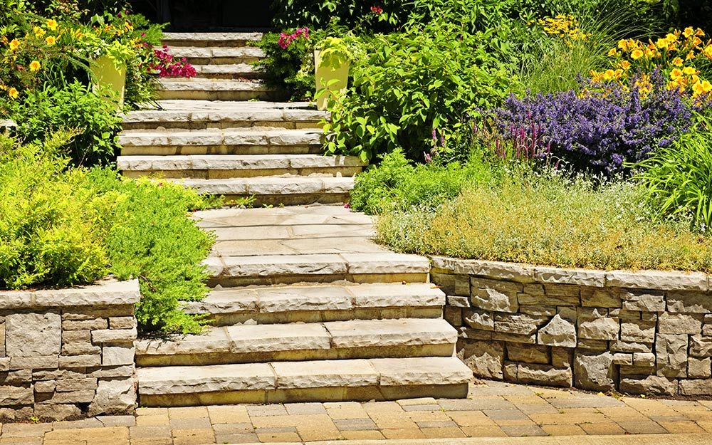 Flower beds in retaining walls next to stone steps.
