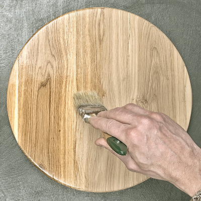 A person applies wood finish to a cutting board with a paint brush.