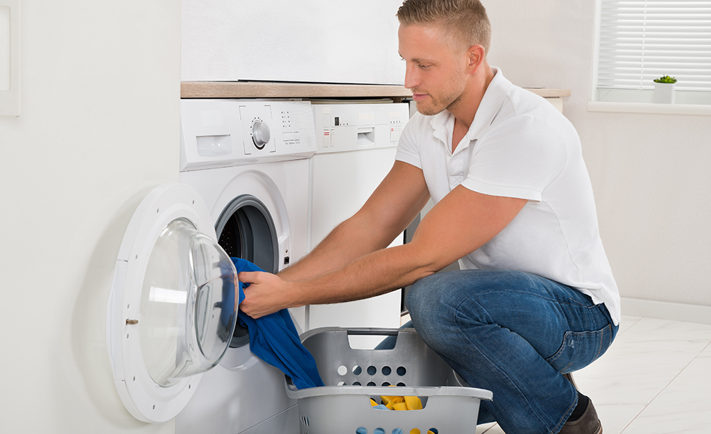 Man adding clothes to front load washing machine.