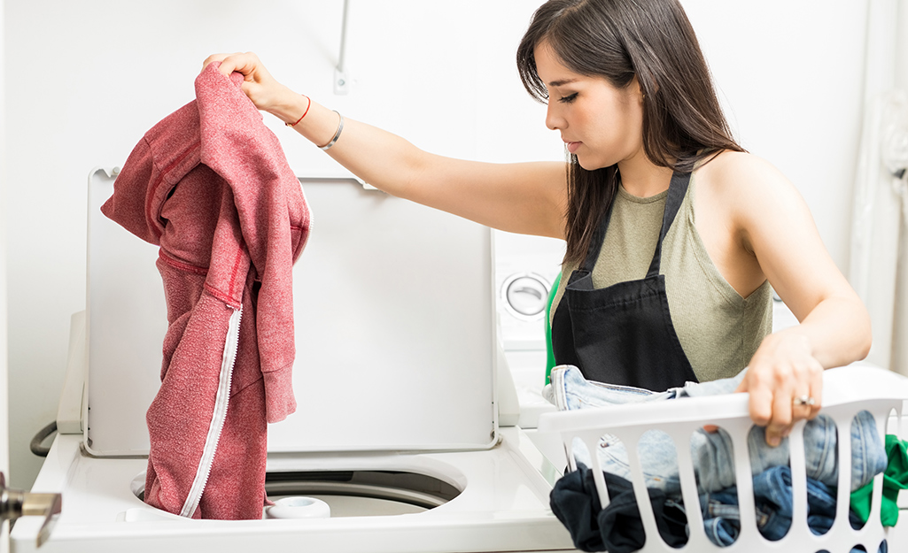 Woman loading laundry into a top load machine.