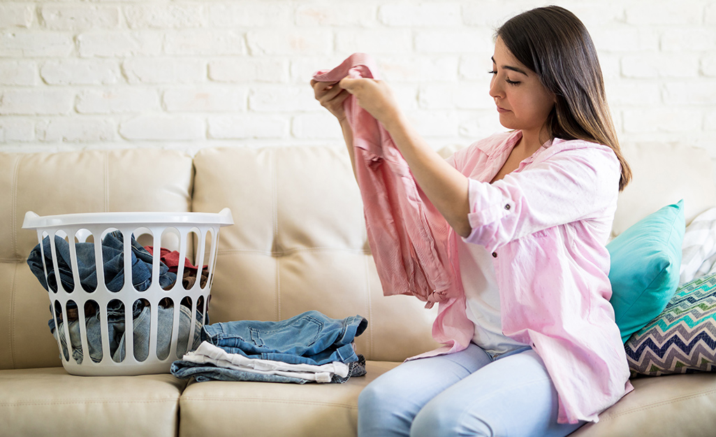 Woman folding clean clothes while sitting on a sofa