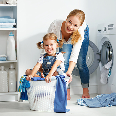 Child in a laundry basket with her mom behind her.