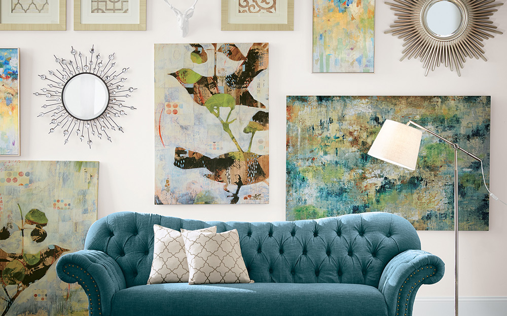 Oversized art prints and mirrors over a blue sofa.