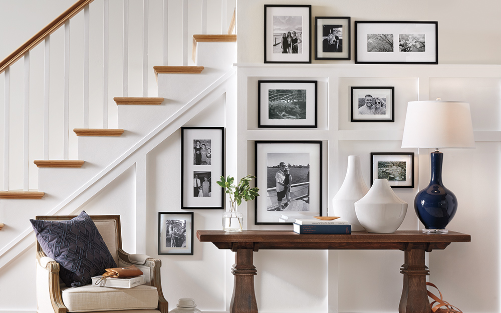 A wall art gallery of black and white photos on a staircase.