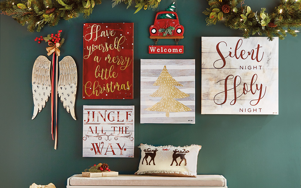 A wall gallery of seasonal word art and wooden wings on a green wall.