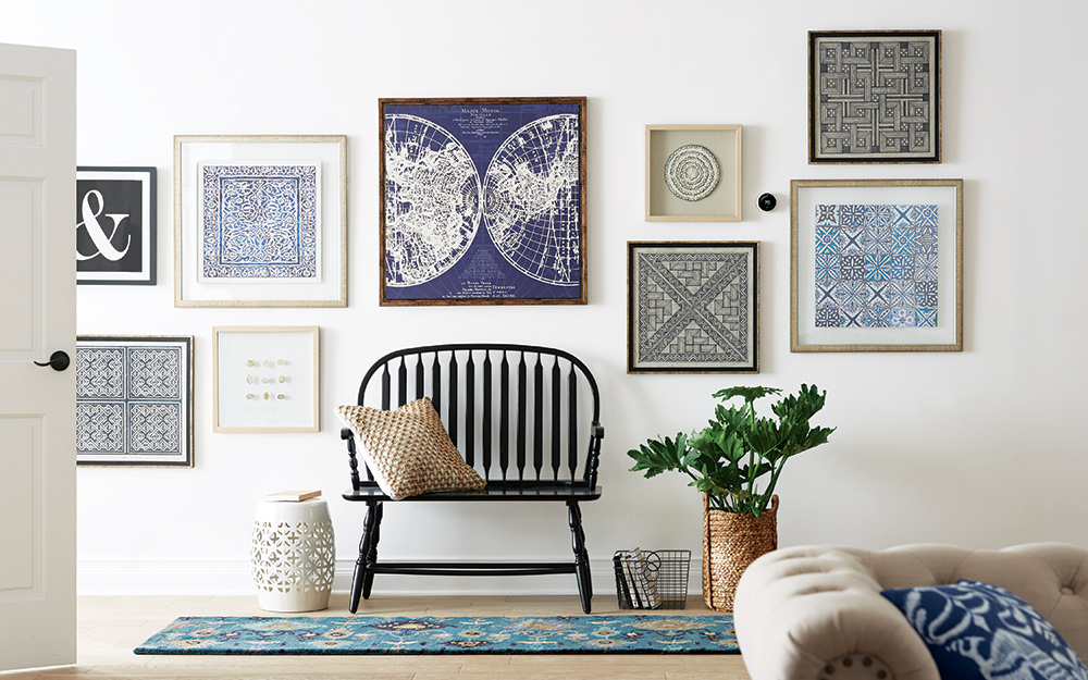 A gallery wall of art over a bench at the front door.