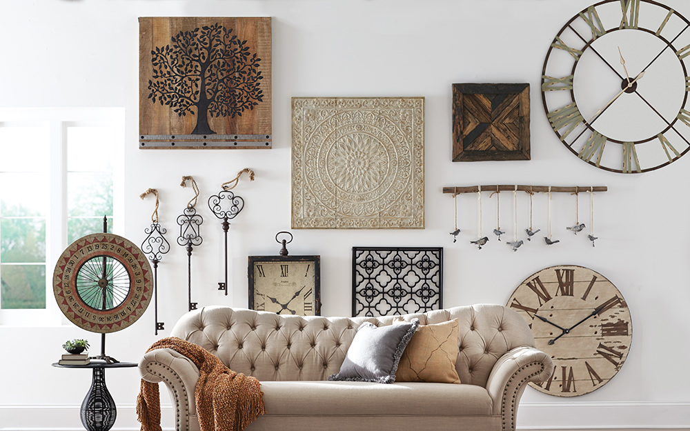 Oversized clocks and wall art on a large wall over a couch.