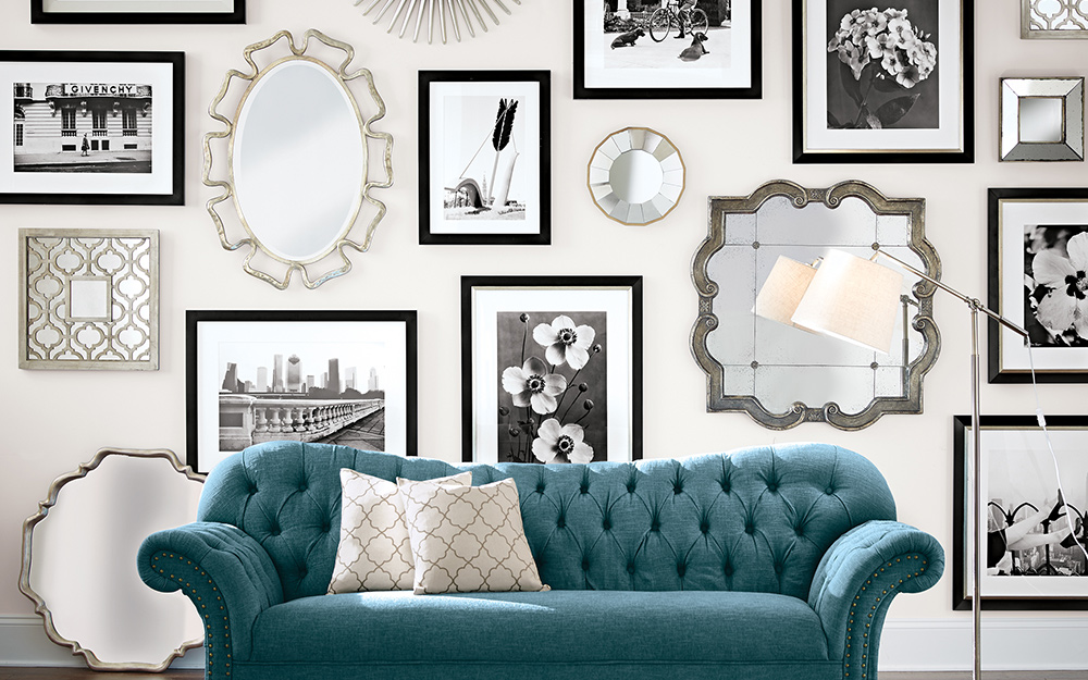 Silver mirrors and black and white wall art displayed over a blue sofa.