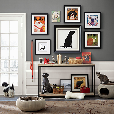 A gallery wall of pet art next to a black and white dog.