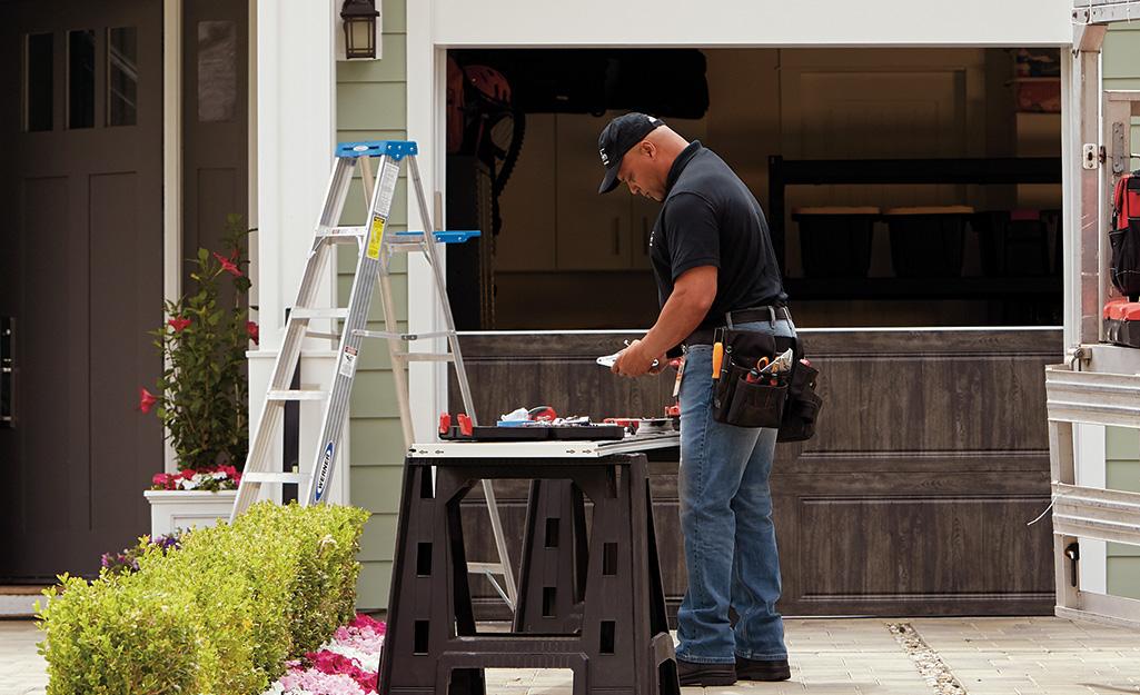 A man gathers tools for garage door maintenance.