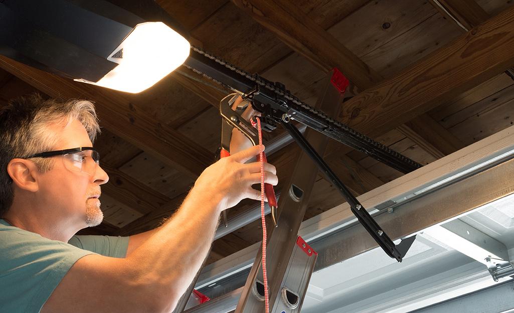 A person adjusts a garage door spring.