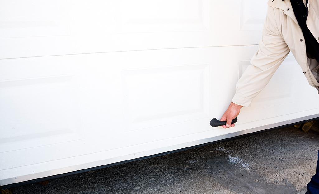 A man manually raises a garage door.