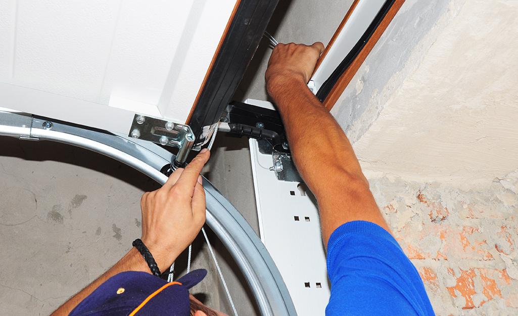 A man inspects garage door hardware.