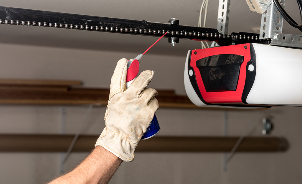 A person oils a garage door chain.