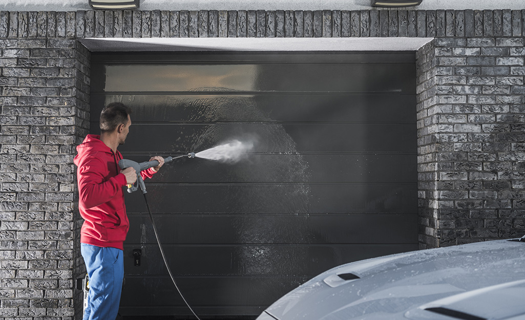 A person cleans a garage door with a pressure washer.