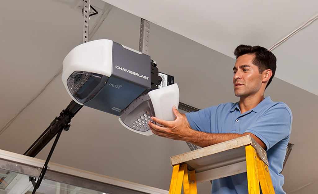 A person stands on a ladder to remove the cover of a garage door motor.