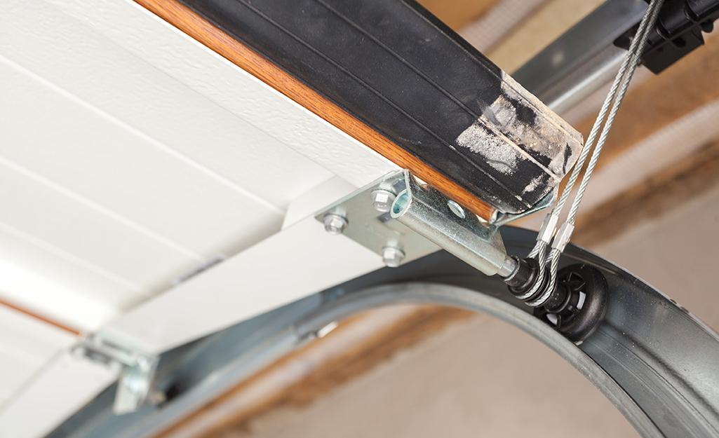 A wheel rolls in the track of a garage door.