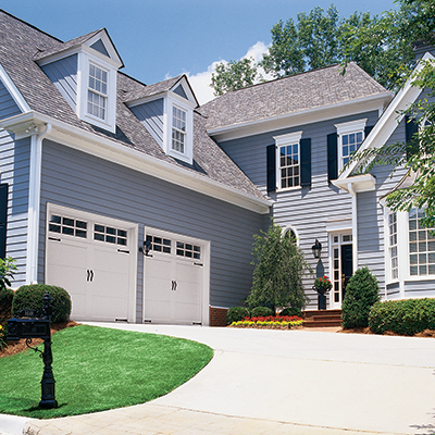 A home with garage doors at the end of the driveway.