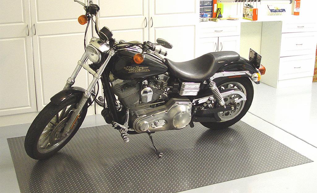 Một chiếc xe máy đang đậu trên tấm lót sàn trong nhà để xe.