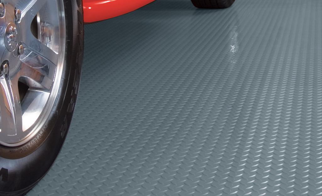 Ô tô đỗ trên tấm thảm lót sàn nhà để xe có hoa văn hình đồng xu được nâng lên.