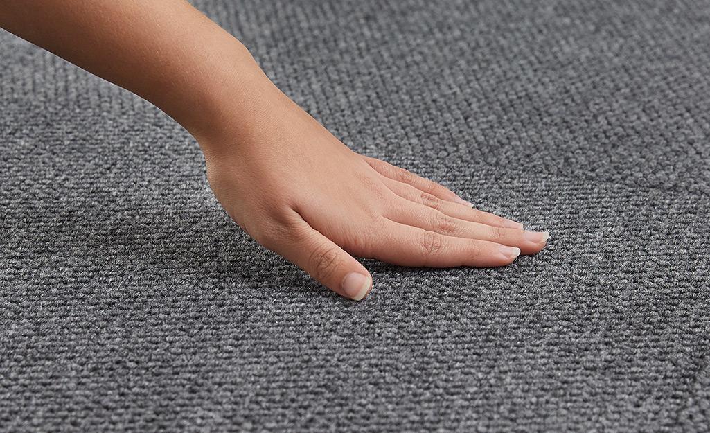 Một người chạm vào một tấm thảm trong nhà / ngoài trời màu xám phù hợp cho nhà để xe.
