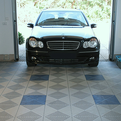 A car enters a garage with patterned tile flooring.