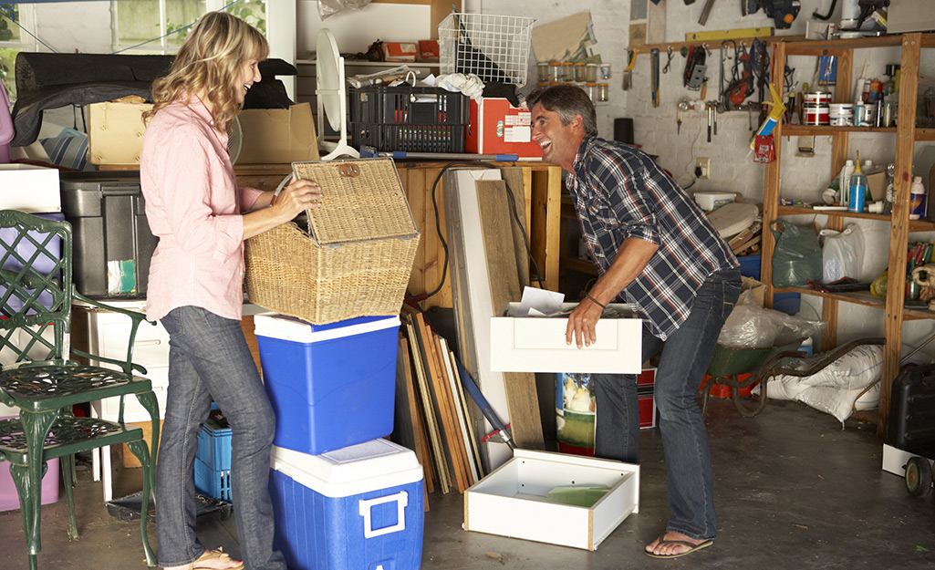 A couple cleans out a cluttered garage.