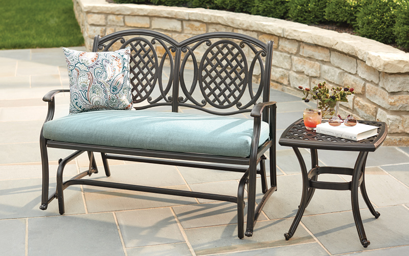 A decorative outdoor loveseat with a small metal occasional table.
