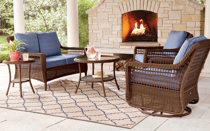 A decorative outdoor rug under a patio set and outdoor fireplace