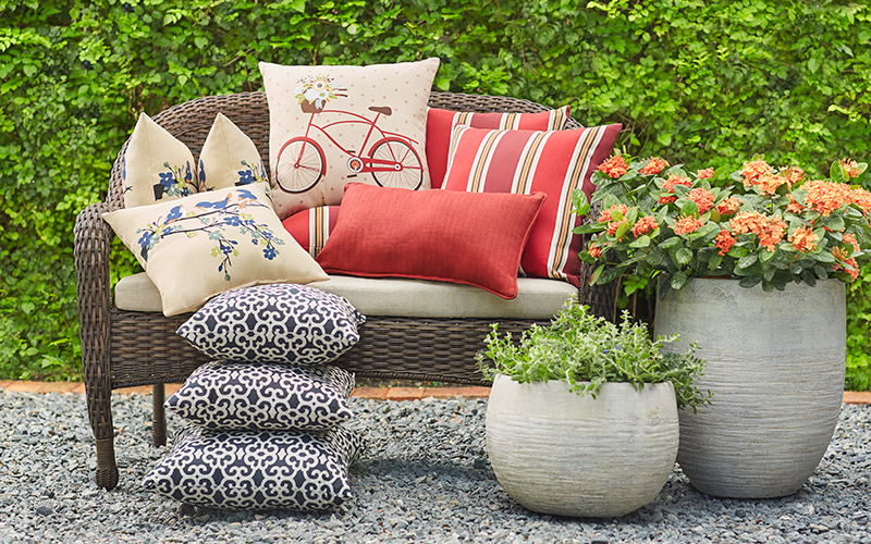Stacks of colorful outdoor pillows on a patio love seat beside two stone planters.