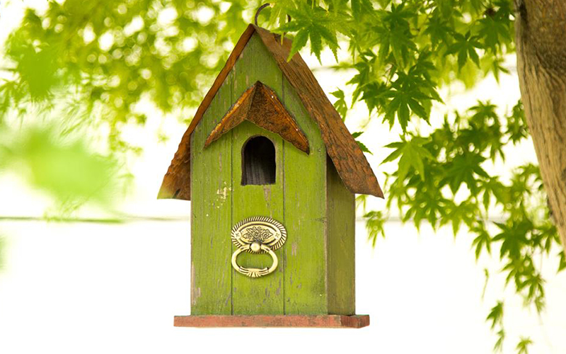 A green birdhouse with a decorative silver door knocker