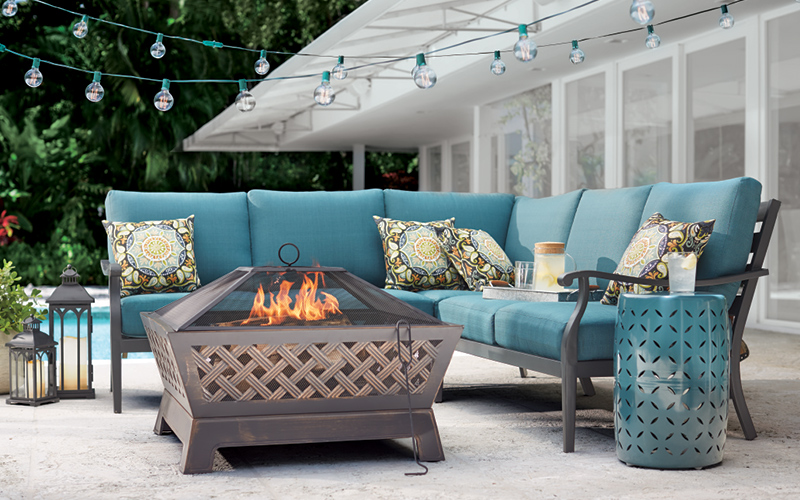 Globe lights strung over a teal patio sectional sofa.