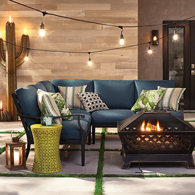 An outdoor living space with items of outdoor decor including lights and a fire pit.