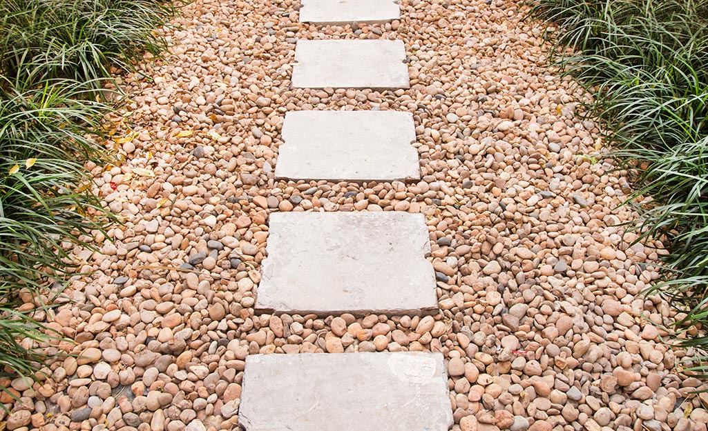 A paver path on a base of landscaping rocks.