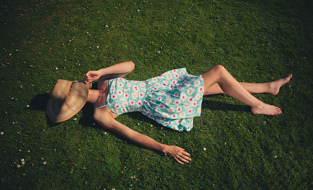 Woman in blue sundress on green lawn