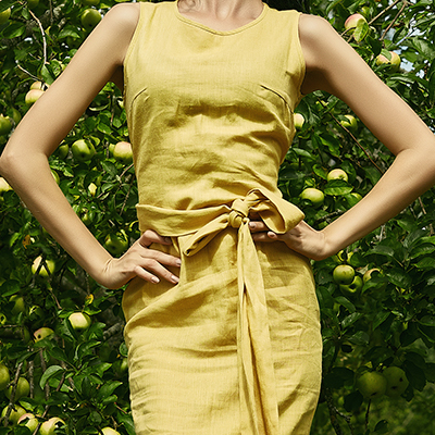 Woman in a yellow linen dress in front of pear tree