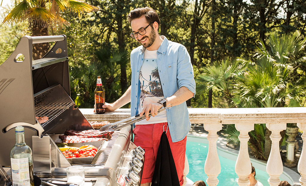 A person uses tongs to turn food cooking on a gas grill.