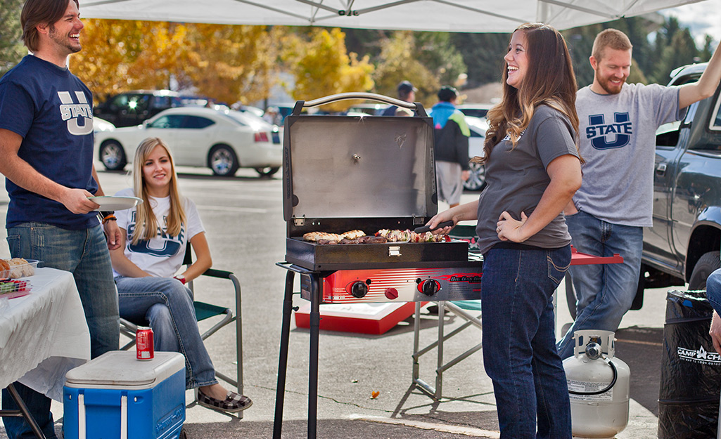A person cooks food on a portable propane gas grill at a tailgate party.